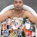 "Ramekon O'Arwisters in a bathtub of dinnerware for ""Smooth the Edges"""