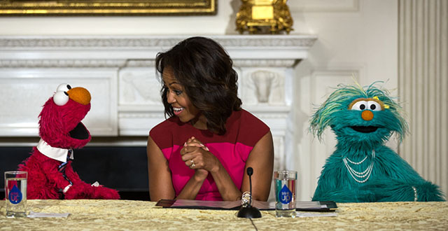 "Michelle Obama with Sesame Street Muppets Elmo and Rosita, makes a ""Let's Move!"" announcement about marketing healthier foods to children, in the State Dining Room of the White House, Oct. 20, 2013. (Official White House Photo by Lawrence Jackson)"